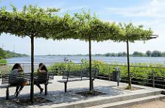 Promenade mit Sitzbänken unter Bäumen an der Elbe bei Geesthacht.