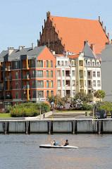 Blick über den Fluß in Elbląg / Elbing; ein Kanu fährt flussaufwärts - Neubauten von Wohnhäusern, Dach der Kirche zur Heiligen Jungfrau Maria.