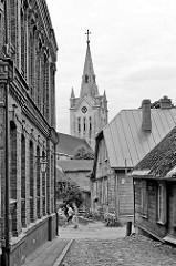 Altstadt von Cēsis, Lettland - historische Architektur, Strasse mit Kopfsteinpflaster - Kirchturm der Ende des 13. Jahrhundert erbauten St. Johanniskirche.