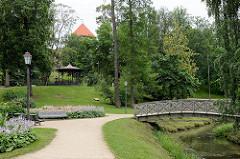 Schlosspark von Cēsis,  angelegt 1812; Eisenpavillon - Holzbrücke, Ruhebänke. Im Hintergrund Burgturm der Ordensburg.