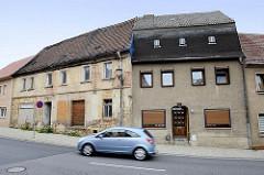 Wohnhäuser in Strehla - restauriertes Gebäude mit Rauhputz - leerstehendes Haus mit abgesprungenem Putz und vernageltem Fenster.