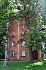 Ziegelturm bei der Sankt Simons Kirche in Valmiera; lks. das Denkmal für Janis Neiland, Theologe und Komponist.