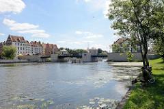 Ein Angler sitzt am Flussufer der Elbląg / Elbing - Neubauten am gegenüber liegenden Ufer.