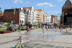 Kirchenvorplatz  mit Brunnen in Elbląg / Elbing - Kinder spielen in der Sonne - im Hintergrund Neubauten mit teilw. historisierenden Fassaden.