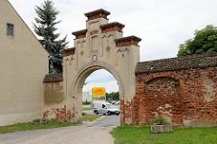 Torweg / Klostertor und alte Ziegelmauer vom Kloster Marienstern in Mühlberg, Elbe - dahinter ein Supermarkt.