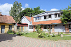 Holzgebäude als Neubau - angrenzende alte Schuppen, blühende Rosen im Innenhof; Architekturbilder in Kuldīga / Lettland.