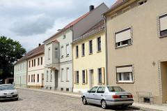 Schlichte einstöckige Wohnhäuser mit  Putzfassade - Straße mit Kopfsteinpflaster; Architektur in Mühlberg / Elbe.
