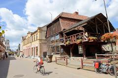 Geschäftsstraße / Fussgängerzone Baznīcas iela  in Kuldīga / Lettland. Holzhaus, Restaurant mit Holzterrasse.