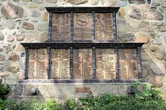 Denkmal für die Gefallenen des I. Weltkriegs aus dem Kirchspiel Hittfeld - Den Vätern und Söhnen, die fürs Vaterland starben. Terrakotta-Tafeln mit Zierstäben an der Kirchenaussenwand der St. Mauritius.