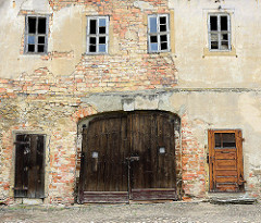 Altes Holztor - unverputzte Ziegelsteine und kaputte Fenster - Wirtschaftsgebäude vom Schloss Strehla.
