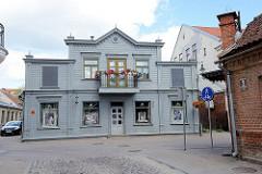 Historische Holzarchitektur - Fassade taubenblau gestrichen, Eisenbalkon mit roten Geranien; Architekturbilder aus Kuldīga / Lettland.