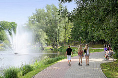 Mädchen / Spaziergängerinnen im Stadtpark / Mühlensee, dzirnavu ezerins von Valmiera, Lettland; Springbrunnen, Wasserfontaine.