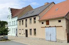 Gebäude am Hafen von Mühlberg / Elbe; Wohnhaus im Baustil der Gründerzeit, schlichtes Wohngebäude mit Rauhputzfassade - Speichergebäude / Garage mit großem Schiebetor.