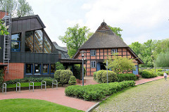 Moderner Neubau der Bücherei Meckelfeld - historisches Bauernhaus / Reetdachhaus / Fachwerkhaus im alten Dorfkern von Meckelfeld.