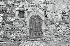 Alte Mauer, Holztür und vergittertes Fenster - Schloss Mühlberg / Elbe.