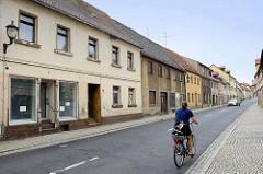 Leerstehende Wohnhäuser, Geschäfte in der Hauptstraße von Strehla, B 182 - Fahrradfahrerin mit Fahrradkorb.