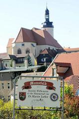 Schild: Mansfeld Herzlich Willkommen in der Heimatstadt von Dr. Martin Luther; im Hintergrund die St.-Georg-Kirche, erbaut ab 1397 - Luther war dort Ministrant.