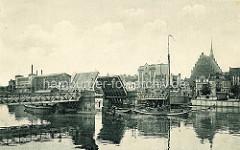 Altes Bild von einer Klappbrücke in Elbląg / Elbing - die Durchfahrt ist geöffnet, ein Ewer fährt flussabwärts. An Land Industriearchitektur - Fachwerkgebäude und die Kirche zur Heiligen Jungfrau Maria.