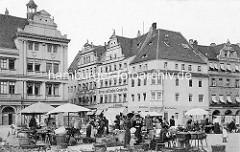 Historische Geschäfts- und Wohngebäude am Markt von Torgau. Marktstände mit Körben, Gemüse - Marktverkäuferinnen; Fassadenaufschrift Herren- und Knaben Garderobe,