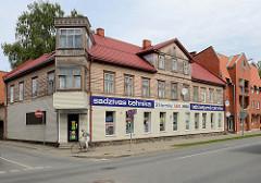Eckhaus - Holzgebäude mit eckigem Erkerturm - daneben ein modernes Wohnhaus mit Ziegelfassade; Architekturbilder aus Valmiera / Lettland.