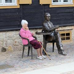 Bronzeskulptur in der Altstadt von Kuldīga / Lettland; sitzender Mann am Bistrotisch.