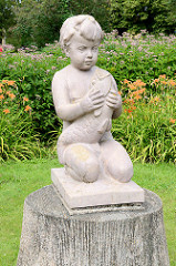 Steinskulptur, nackter Junge mit Fisch im Stadtpark von Valmiera, blühende Blumen.