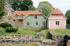 Historische Holzhäuser  auf der Burg des Livländischen Ritterordens aus dem 13. Jahrhundert in Valmiera, Lettland. Die Anlage wurde im Nordischen Krieg 1702 zerstört und ist nur als Ruine erhalten.