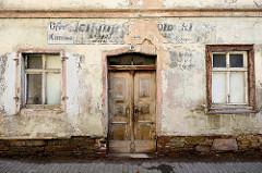 Alte Hausfassade mit Holztür und Fenstern - verlassenes, leerstehendes Gebäude in Mansfeld an der Rabentorstraße.