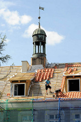 Handwerker beim Restaurieren eine Gebäudes in Elbląg / Elbing, Dachdecker bei der Arbeit.