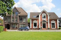 Wohnhäuser / Geschäftshäuser in der Kirchstraße von Hittfeld; historischer Altbau, moderner Neubau mit Dachgiebel.