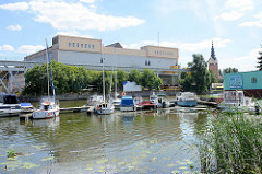Blick über die Marina am Fluss Elbląg / Elbing zu Industrieanlagen am Hafen - re. der Kirchturm der katholischen St. Nikolaikirche.