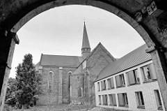 Blick durch einen Torbogen zur Klosterkirche Marienstern in Mühlberg / Elbe. Das Zisterzienserinnenkloster wurde 1228 gegründet; die einschiffige Klosterkirche ist ein gotischer Backsteinbau mit romanischen Elementen.