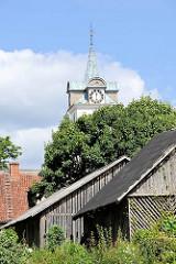 Holzschuppen und Kirchturm der Römisch-katholische Kirche der Heiligen Dreifaltigkeit in Kuldiga, Lettland.
