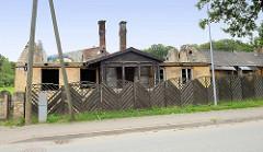 Ausgebranntes Wohnhaus - Brandruine, Schornsteine ragen in den Himmel; Holzzaun - Bilder aus Cēsis / Lettland.