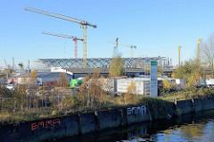 Gewerbegebiet am Oberhafenkanal - Parkplatz für Lastwagen, Lagerhallen; im Hintergrund die Baustelle der Haltestelle Elbbrücken in der Hamburger Hafencity.