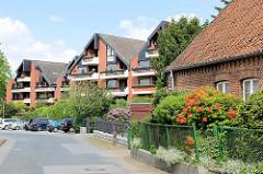 Moderne Wohnhäuser - Architektur der 1980er Jahre - altes Backsteingebäude mit blühenden Azaleen im Vorgarten - Bilder aus Hittfeld / Seevetal.