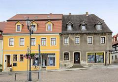 Wohnhäuser am Markt von Strehla - unterschiedliche Fassadengestaltung, frisch renoviert mit gelber Fassade und neu gedecktem Dach - grauer Rauhputz mit holzverkleideten Dachfenstern.