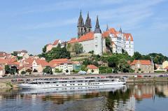 Blick über die Elbe; das Flusskreuzfahrtschiff Elbe Princesse liegt an der Elbpromenade - dahinter der Burgberg mit der Albrechtsburg in Meißen - spätgotisches Architekturdenkmal, einer der ersten Schlossbauten in Deutschland; errichtet 931. Da