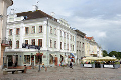 Rathausplatz von Tartu; klassizistische Architektur - Restaurant / Aussengastronomie mit Sonnenschirmen auf dem Platz.