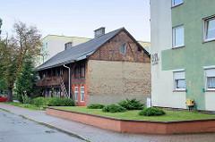 Historische Wohnhaus mit Fachwerk und Laubengang zwischen Beton-Wohnblocks in Toruń.
