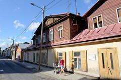 Häuserzeile, Straßenbebauung - Holzhäuser; Wohnhäuser / Reihenhaus mit Fensterläden und breiten Dachfenstern mit Holzverkleidung. Architektur auf dem Baltikum in Tartu.