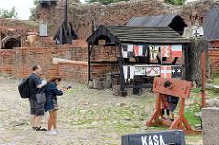 Souvenirladen und gebührenpflichtiger Eingang zur Ordensburg in Torun - ein Kind steht für ein Foto der Eltern am Pranger.