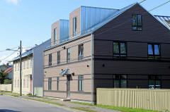Moderner Neubau mit rechteckigen, kubischen Dachfenstern, dahinter älteres Wohnhaus mit Holzfassade; Architektur in Tartu.