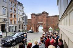 Historische Stadtbefestigung von Toruń - Stadtmauer mit Stadttor / Segeltor. Touristengruppe beim Sightseeing / Stadtführung vor dem Pałac Dąmbskich.