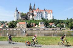 Radwanderweg am Elbufer in Meißen - am anderen Ufer der Burgberg mit der Albrechtsburg - spätgotisches Architekturdenkmal, einer der ersten Schlossbauten in Deutschland; errichtet 931. Dahinter der St. Johannis und St. Donatus Dom, Baubeginn um