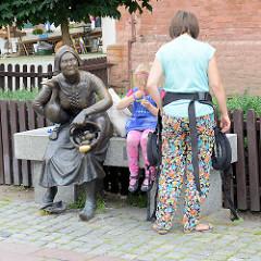 Marktfrau - Bronzeskulptur auf einer Bank, Marktplatz in Toruń - Platz Rynek Nowomiejski, Bildhauer Anety + Macieja Jagodzinskich-Jagenmeer 2011.
