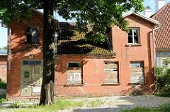 Leerstehendes Wohnhaus  mit vernagelten Fenstern und zerbrochenen Fensterscheiben; Straße Lai in Tartu.