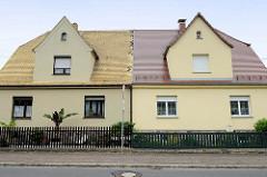 Doppelhaus in Schildau - symmetrische Wohnhäuser mit unterschiedlicher Dachdeckung und Vorgarten / Zaun.