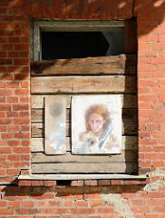 Leerstehendes Wohnhaus mit Holzbrettern vernageltes Fenster - farbiges Frauenportrait; Straße Lai in Tartu.