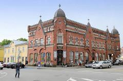 Geschäftsgebäude mit Ziegelfassade - aufgesetzten Giebeln; Turmelemente mit Kupferdach - Rüütli in Pärnu.